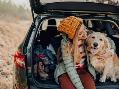 A smiling woman and her dog sit in the open hatch of a station wagon