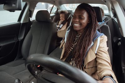 A mother is in the drivers seat of her car. Two children are in the back seat.