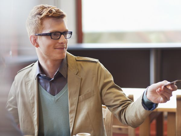 A young man in eyeglasses hands a credit card to someone or something unseen out of frame to his left.