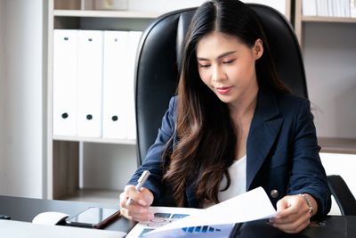 Woman sitting at desk going over financial papers