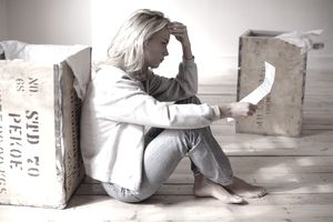 a woman looking distressed reading a lease agreement in empty apartment with boxes next to her