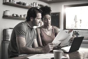 A man and a woman are in a kitchen reviewing documents.