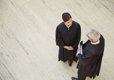 Overhead view of two judges talking in a courthouse corridor