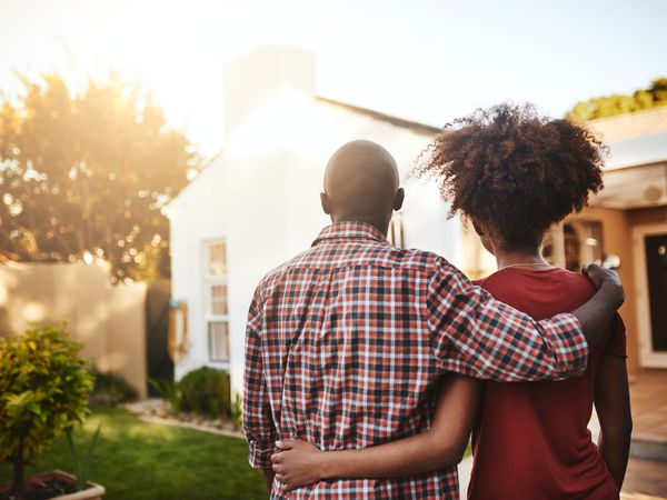 A couple stands outside with their arms around one another, gazing away from the camera at their first house, which is bathed in sunlight