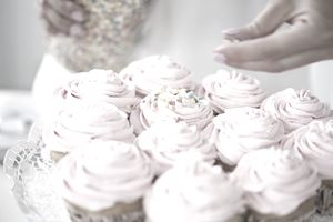 A plate of delicately frosted pink cupcakes rests beneath the hand of a baker deftly applying sprinkles.