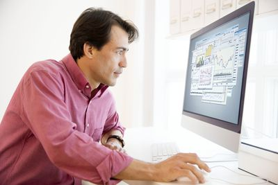 man investing in stocks on computer