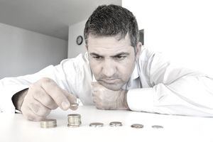 Man resting his chin on his hand counting coins on a counter top, symbolizing bankruptcy.
