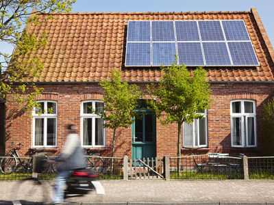 A cyclist bikes past a brick house with solar panels on its roof, which might qualify for a green home insurance discount.
