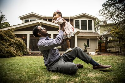 A father holds his toddler daughter in the air a he sits on the lawn in his backyard