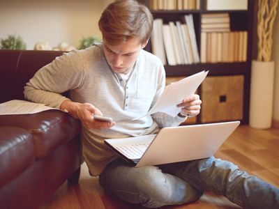 Man sitting on floor, looking at smartphone while working on laptop