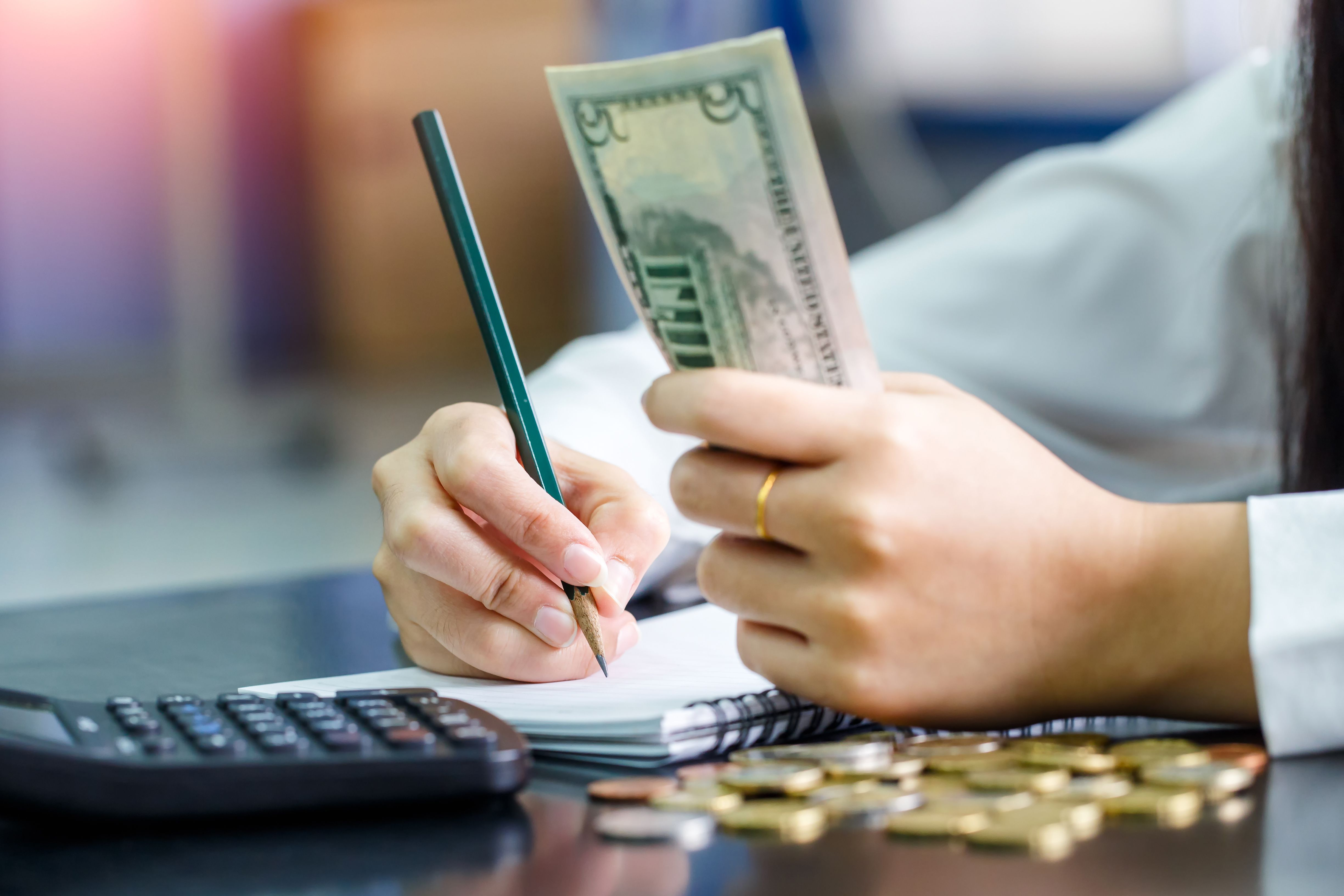 Homeowner clutching five dollar bills in one hand as she calculates her expenses with a pencil, pad, and calculator