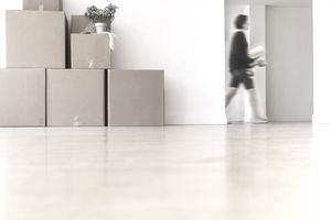 Woman walking near cardboard boxes stacked against wall