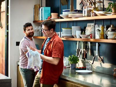 Cheerful male couple washing and drying dishes by hand