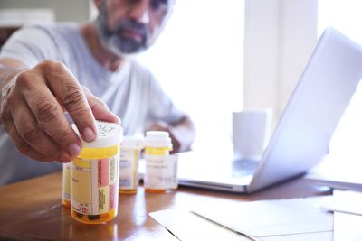 Hispanic Man Sitting At Dining Room Table Reaches For His Prescription Medications