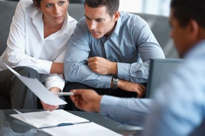 Man and woman consulting with another man holding paperwork in an office.