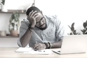 A man cradles his head in his hand, frustrated, while reviewing his smaller than expected tax return