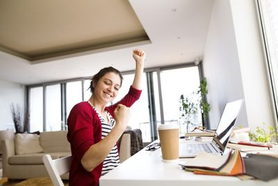 Happy woman fist-pumping at her desk at home