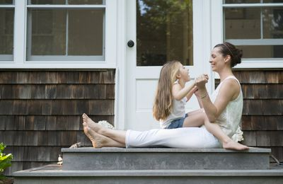 A woman sits on the front steps of a home with a child on her lap