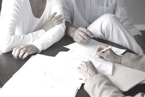 Couple meeting with female financial advisor, close-up of hands