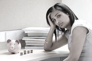 Depressed student at desk with piles of pennies