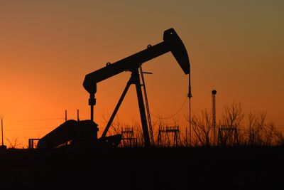 Silhouette Oil Pump Against Clear Sky During Sunset