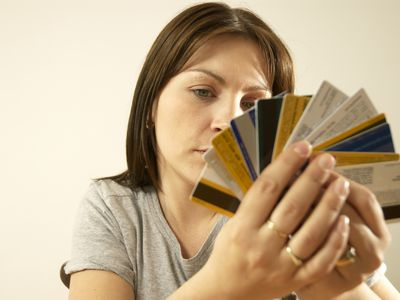 Woman looking overwhelmed by all her credit cards
