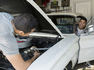A son in the driver's seat laughs at his father who is under the hood of the salvage car they are rebuilding
