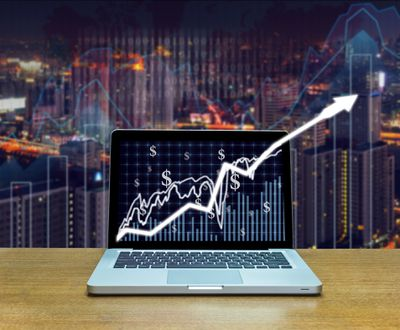 Stock exchange market trading graph leaping off the screen of computer laptop