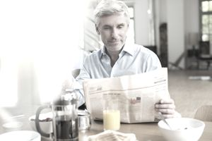 Older man having breakfast and reading the paper