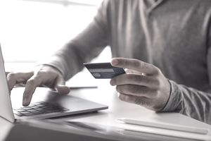 Male wearing a gray sweater holding a credit or debit card and ordering something on a laptop