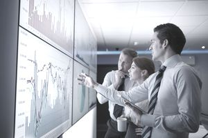 Three business people discuss graphs on screen in meeting room