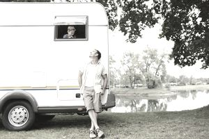 Man outside of RV smiles at child inside it
