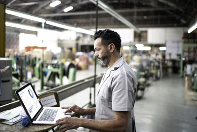 Man using a laptop while working in a factory
