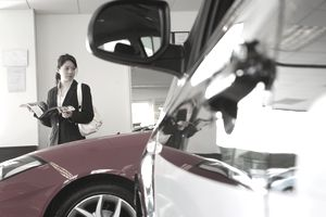 Woman reviewing literature in showroom with vehicles