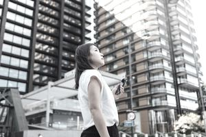 Woman with phone in hand looking at high-rise building