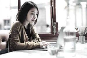 Beautiful Young Woman Using Laptop Sitting At Cafe