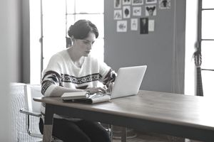 Young person in sweater looks at laptop on table