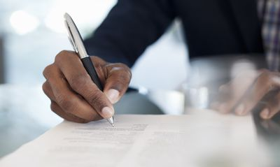 man signing a transfer on death account contract