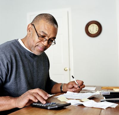 Man using calculator to figure average daily balance finance charges