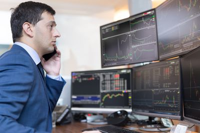 Person on phone trading stocks in front of several computer monitors