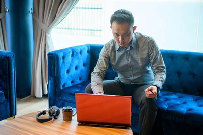 A man sits on a blue velour couch and enters credit card information on a laptop.