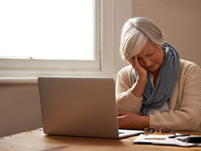 Elderly woman at a laptop looking frustrated while reviewing financial documents