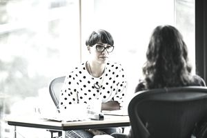 Businesswoman in office at desk speaking with another person