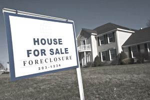 "Closeup of a ""House for Sale-Foreclosure"" sign on the lawn of a residence."