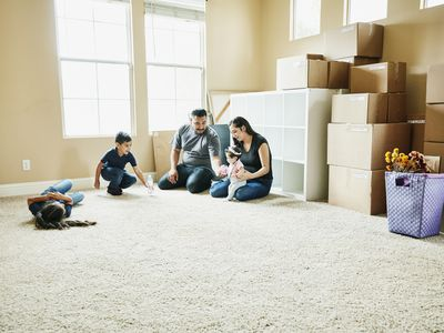 Family sitting on floor of living room of new home during move in day