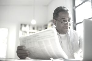 A retired man reading the morning newspaper during a leisurely morning