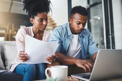 couple sitting on couch filing paperwork with computer in front of them