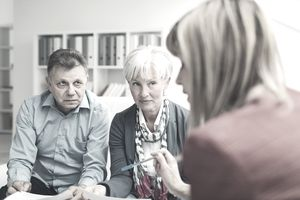 An older couple meeting with a lawyer in her office to discuss identity theft.