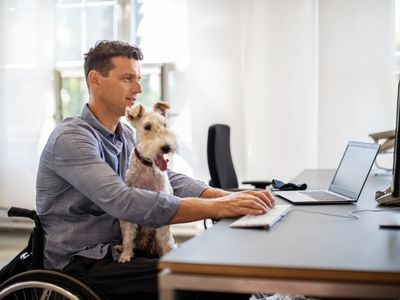 Businessman with his pet dog working on a computer