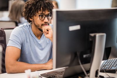 person with glasses staring at desktop computer screen